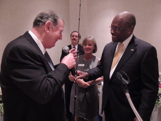 Rick Berry presenting fishing rod to Herman Cain, our keynote speaker